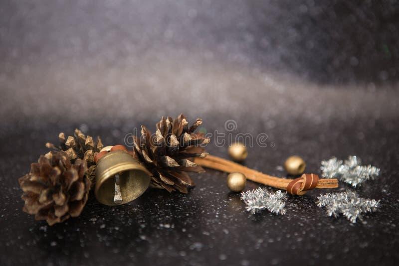 圣诞节与金属响铃的背景黑色和两棵杉木、银闪耀的雪花星和金球 免版税库存照片