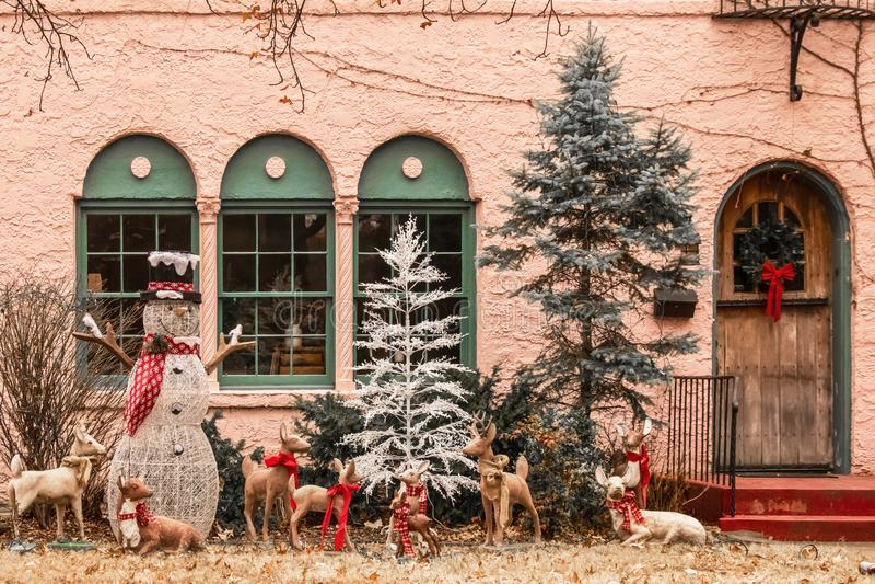 圣诞节与雪人和有饰缎带鹿的森林场面桃红色灰泥房子外窗口  免版税库存图片