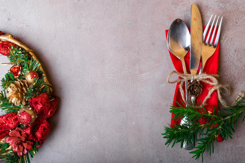 圣诞节从红色花圈的冬天背景与在石桌上的银色餐位餐具 圣诞节和新年假日,拷贝空间 免版税图库摄影