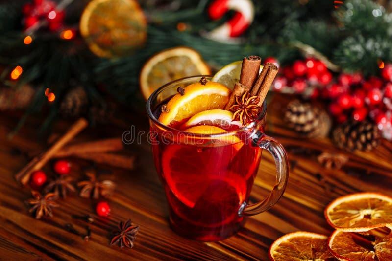 圣诞节仔细考虑了红酒用香料和果子在一张木土气桌上 在冬时的传统热的饮料 图库摄影