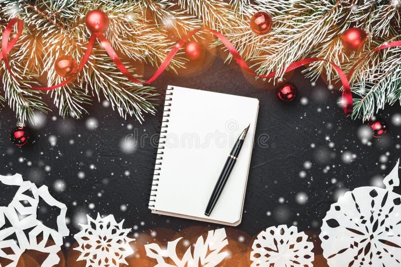 圣诞节信包冷杉节假日霍莉例证信笺纸向量 在黑石背景 冷杉分支用球和红色松驰装饰了 顶视图 免版税库存照片