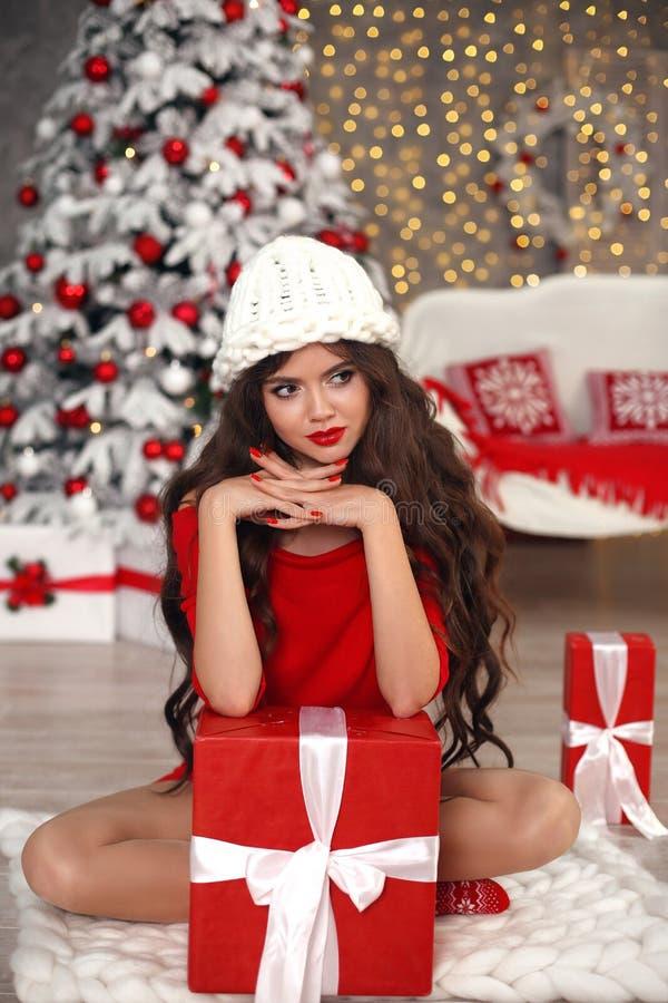 圣诞节修指甲 在冬天帽子的深色的女孩画象 美丽的佩带在有长的红色礼服的圣诞老人妇女当前礼物盒 免版税库存图片
