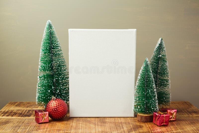 圣诞节假日嘲笑与帆布和杉树在木桌上 免版税库存图片