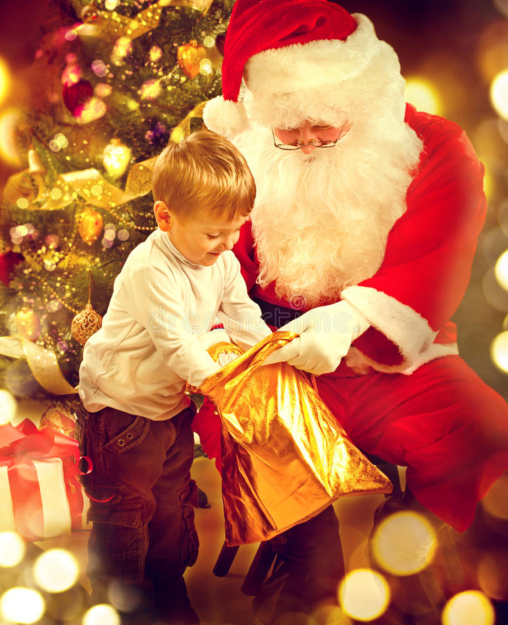 圣诞节假日场面 逗人喜爱的小男孩和圣诞老人 库存图片
