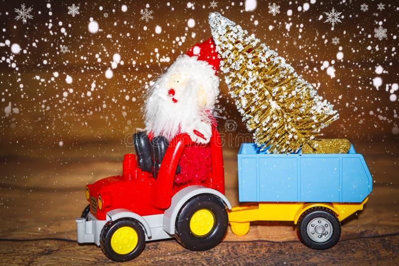 圣诞节假日庆祝题材 圣诞老人运载在拖拉机的圣诞树有拖车的 免版税库存照片