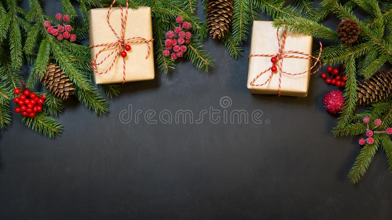 圣诞节假日背景-树、礼物、霍莉莓果和装饰在一黑chackboard 与拷贝空间的假日卡片 视图 免版税图库摄影
