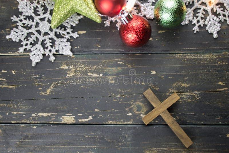 圣诞节假日装饰品和基督徒十字架在黑暗的木头B 图库摄影