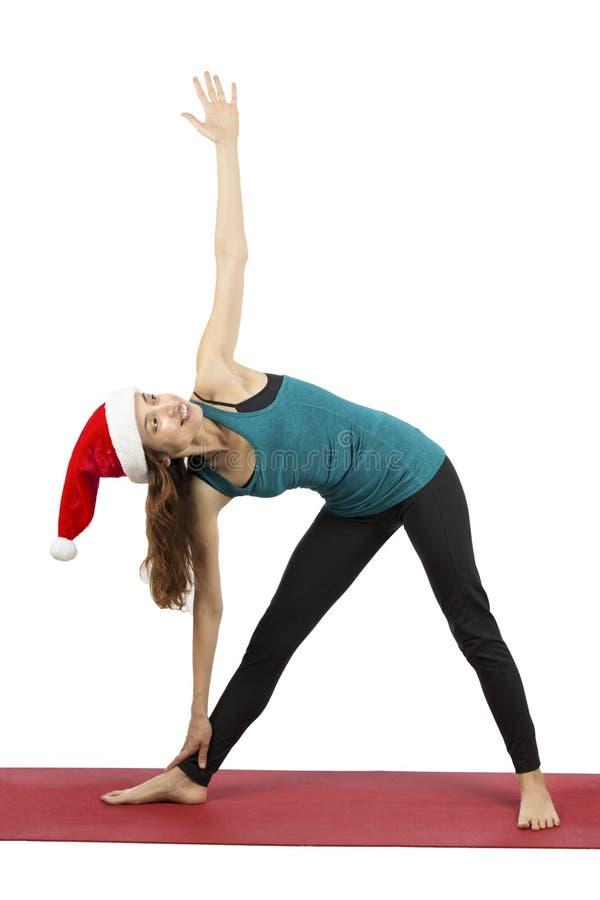 圣诞节做延长的三角姿势的瑜伽妇女 免版税图库摄影