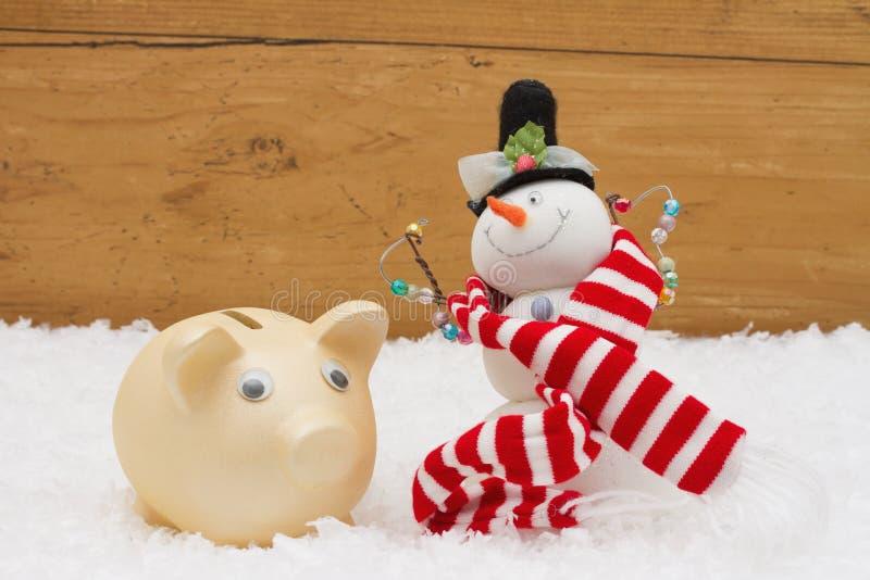 圣诞节储款、存钱罐和雪人与围巾在雪wi 免版税库存图片