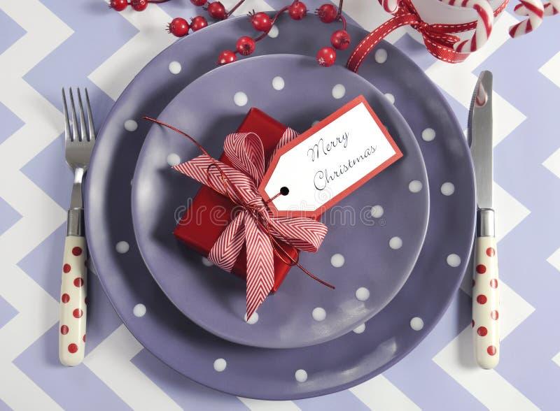 圣诞节儿童家庭党桌在紫色,红色和白色题材的餐位餐具 图库摄影