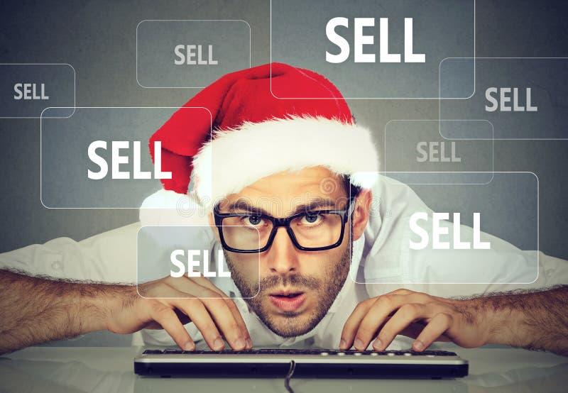 圣诞节卖在互联网上的圣诞老人帽子的商人材料 免版税库存图片