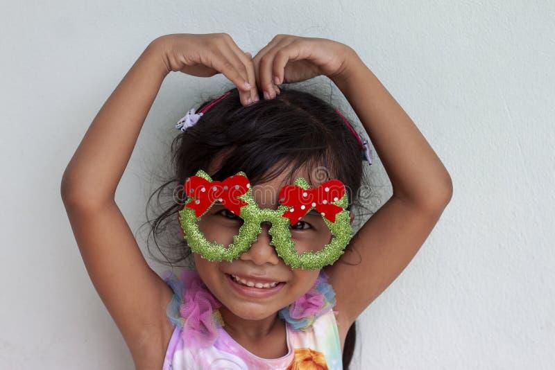 圣诞节和做的心脏形象女孩戴着眼镜在头顶上 免版税库存照片