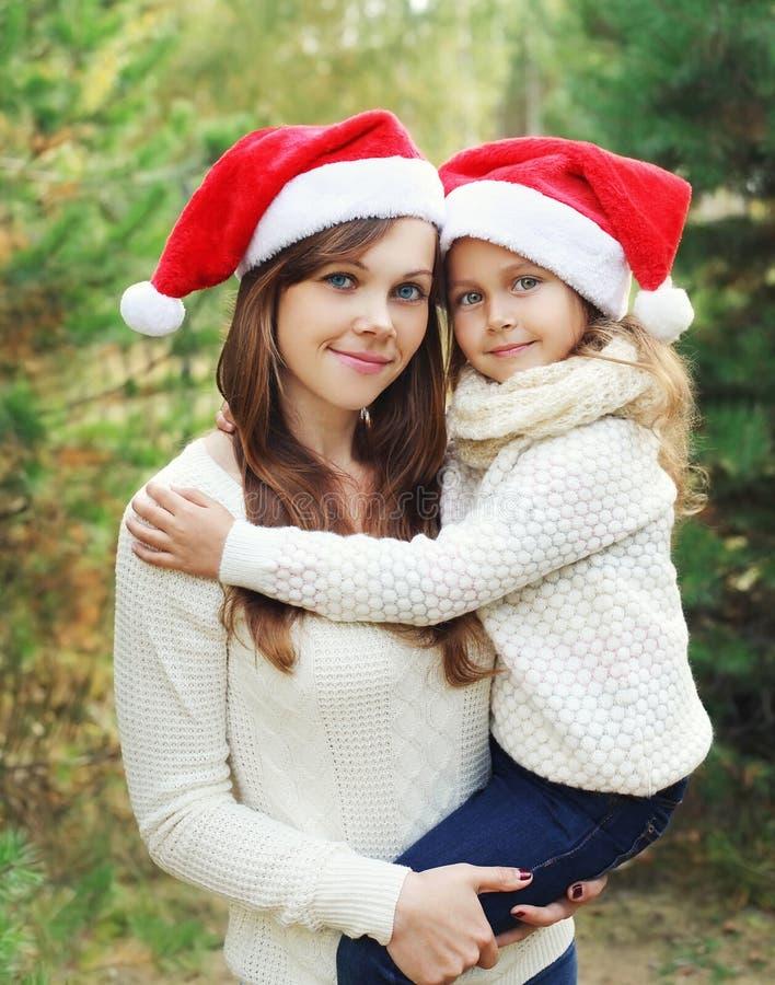 圣诞节和家庭观念-愉快的母亲和孩子获得圣诞老人红色的帽子的乐趣 免版税库存图片