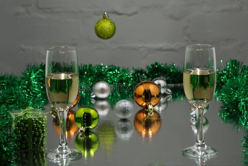 圣诞节和新年假日制表设置用香槟 庆祝 圣诞晚餐的餐位餐具 被点燃的背景电灯泡色的装饰诗歌选节假日光 免版税库存图片