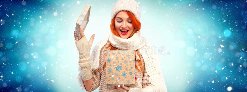 圣诞节和新年假日 有礼物的愉快的readhead妇女 购物妇女藏品在冬天背景的礼物盒 免版税库存照片