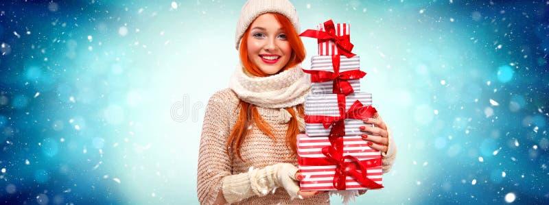 圣诞节和新年假日 有礼物的愉快的readhead妇女 购物妇女藏品在冬天背景的礼物盒 库存照片