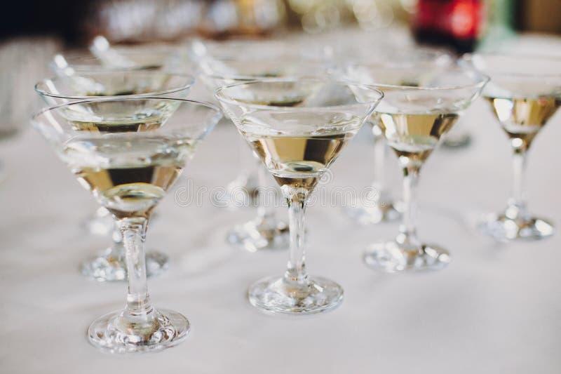 圣诞节和新年宴餐在桌党的马蒂尼鸡尾酒行在结婚宴会 在水晶玻璃的马蒂尼鸡尾酒饮料在酒精酒吧 免版税库存照片