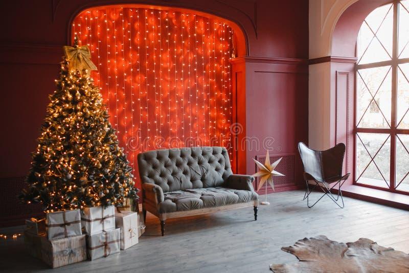 圣诞节和新年装饰了有轻的bokeh诗歌选和新年树的内部室和在红色前面的经典灰色沙发 库存图片