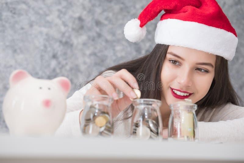 圣诞节和节日的美丽的年轻美丽的女孩挽救金钱 库存图片