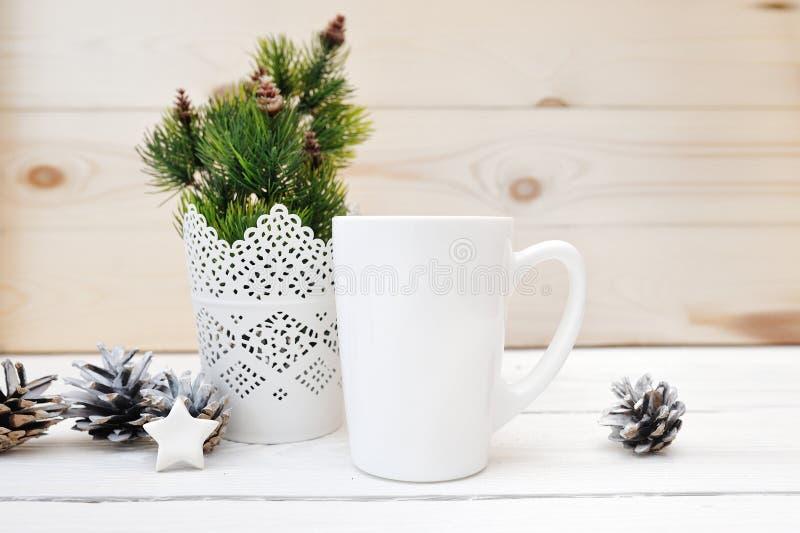 圣诞节嘲笑称呼了储蓄产品形象白色杯子,与您能的一个白色空白的咖啡杯的圣诞节场面 免版税图库摄影