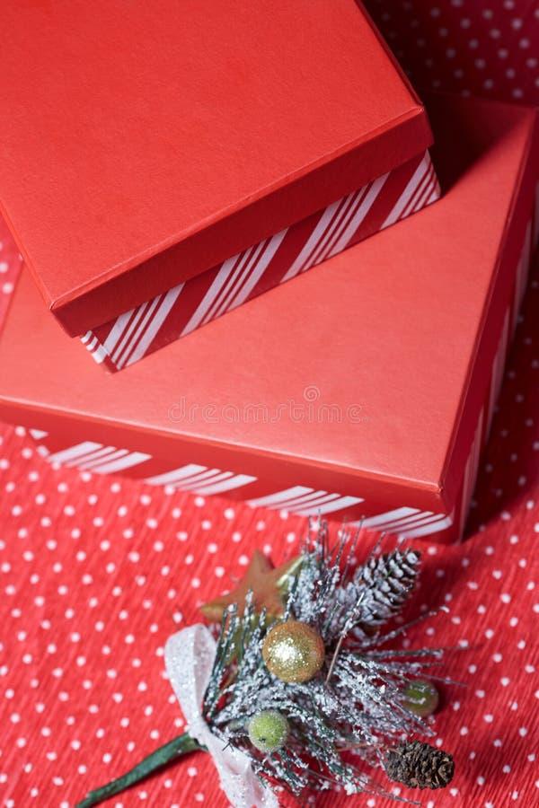 圣诞节圣诞树的礼物盒和枝杈在一红色wrappin的 免版税库存图片
