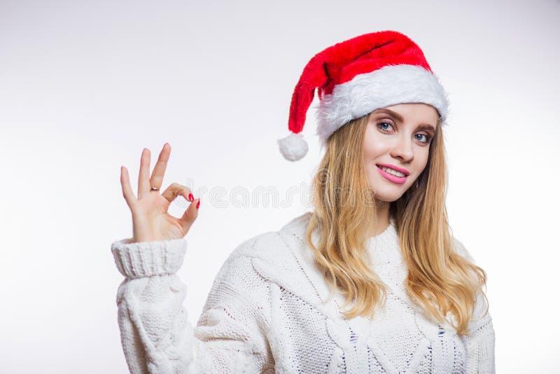 圣诞节圣诞老人妇女画象 穿一个红色帽子和一件米黄被编织的毛线衣的微笑的愉快的女孩显示在白色backg的标志OK 免版税库存图片