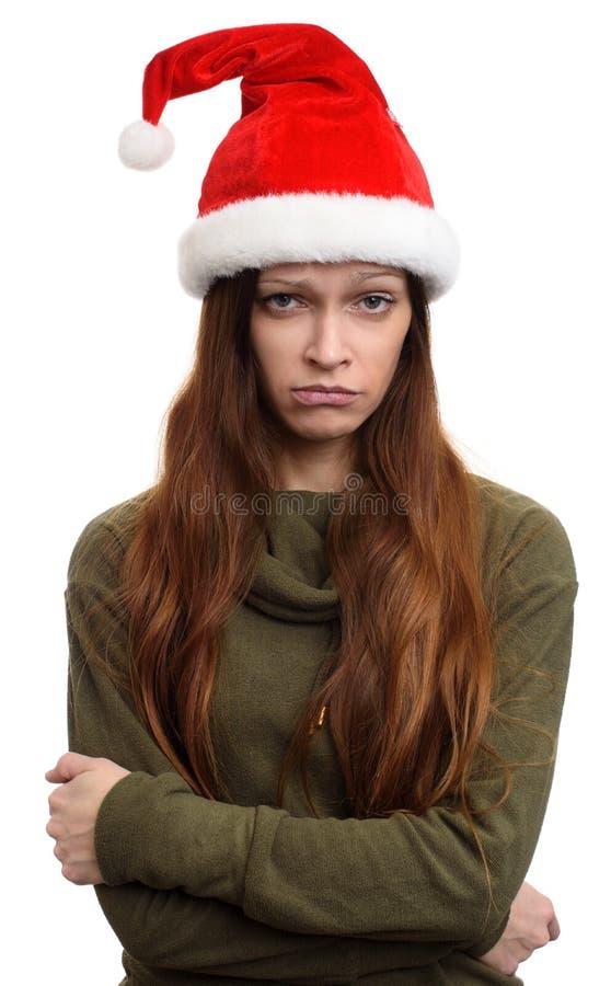 圣诞节圣诞老人帽子的哀伤的女孩 免版税库存图片