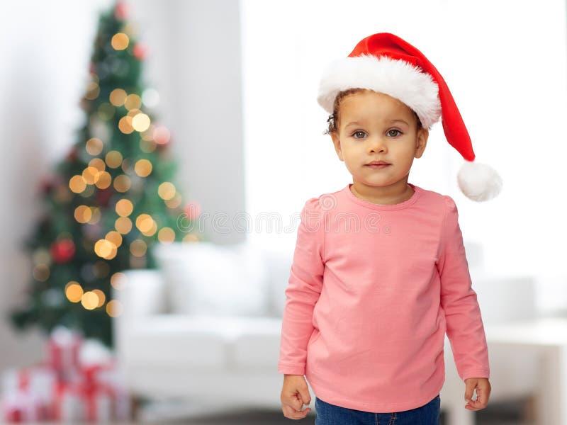 圣诞节圣诞老人帽子的美丽的矮小的女婴 免版税库存照片