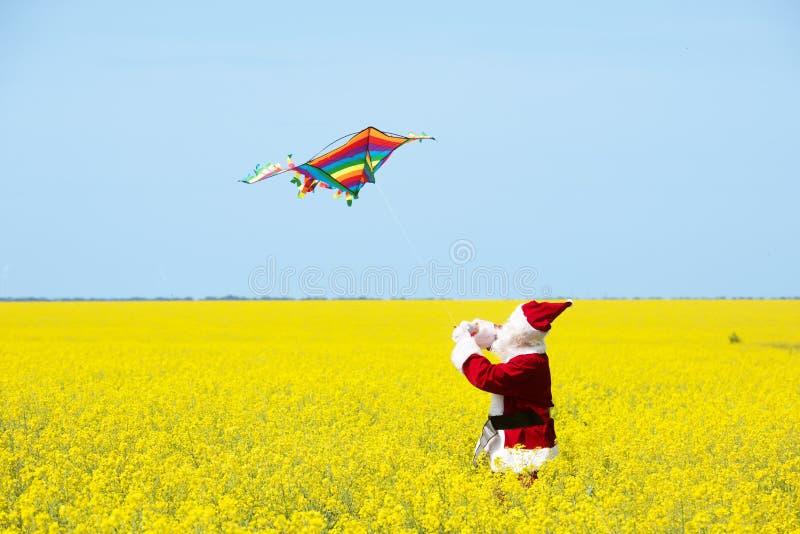 圣诞节圣诞老人项目扔在开花的黄色领域的一只风筝 免版税库存照片