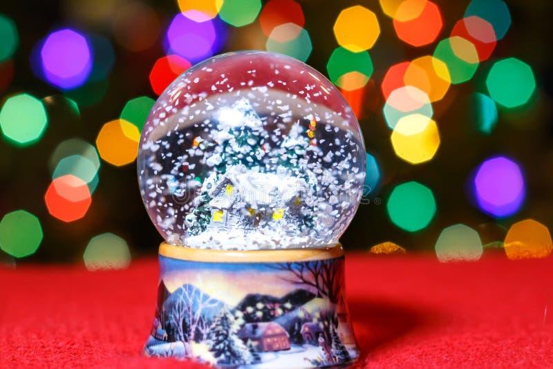 圣诞节在圣诞树前面的雪地球点燃特写镜头 库存照片