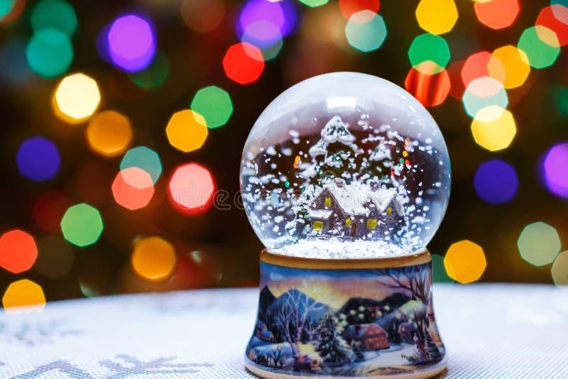 圣诞节在圣诞树前面的雪地球点燃特写镜头 图库摄影