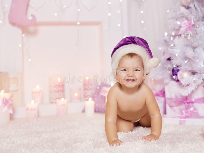 圣诞节在圣诞老人帽子,儿童Xmas桃红色室的婴孩孩子 库存图片