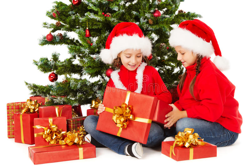 圣诞节在圣诞老人帽子,杉树,儿童开放当前礼物盒哄骗 免版税图库摄影