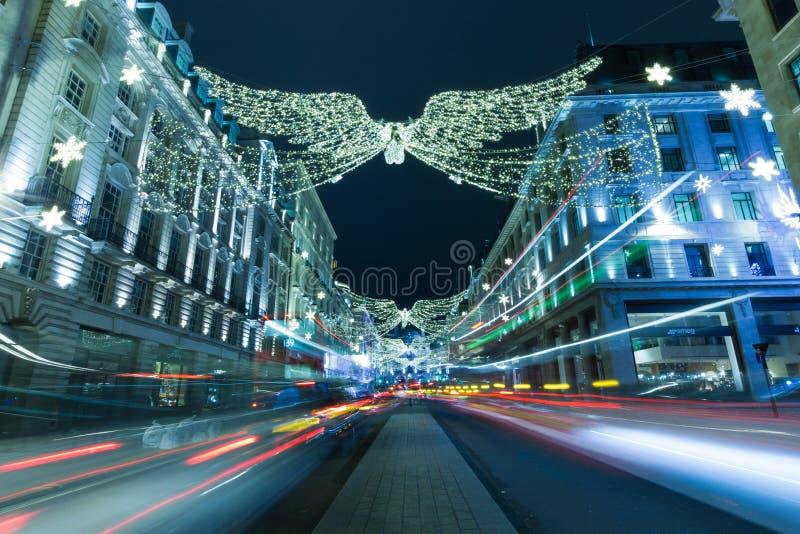 圣诞节在摄政的街道伦敦的天使和装饰光 ?? 从低价的射击摄政的街道在晚上在12月 免版税库存图片