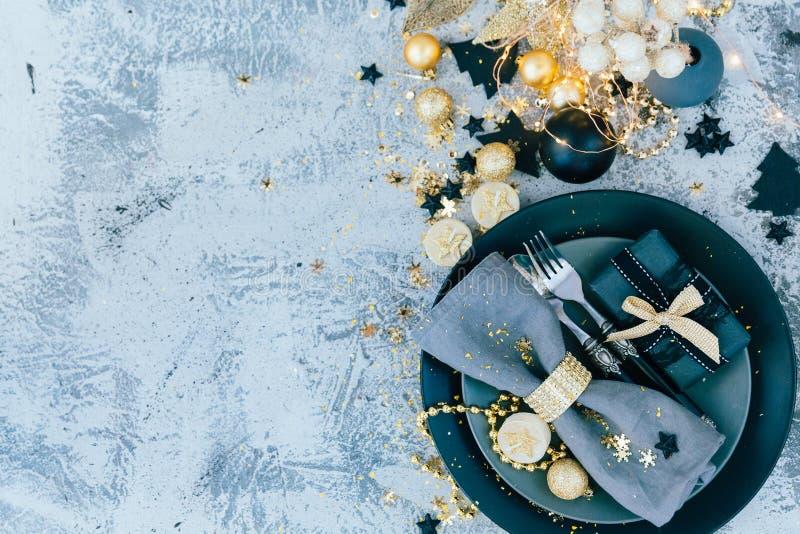 圣诞节在晚餐前的桌设置与金装饰 免版税图库摄影
