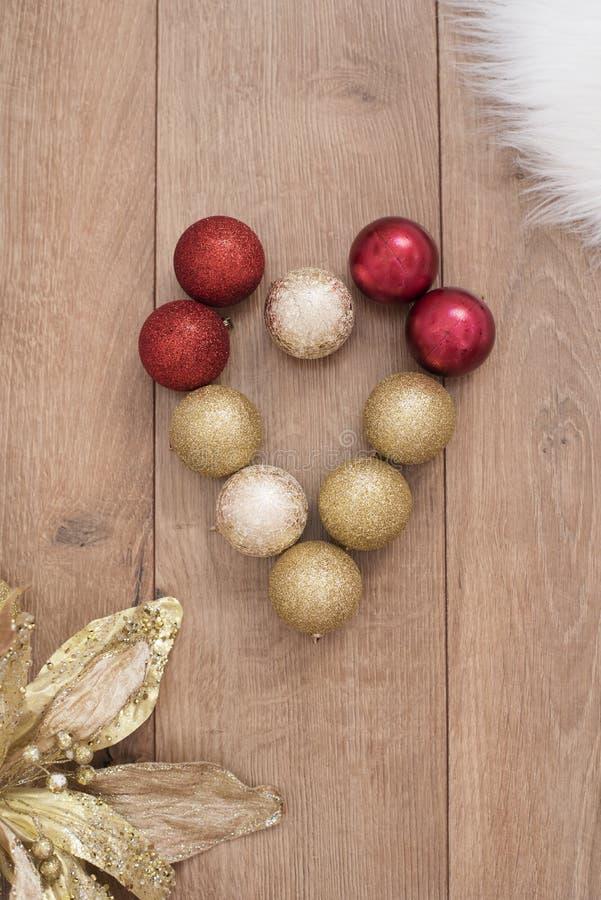 圣诞节在木背景的球心脏 库存照片