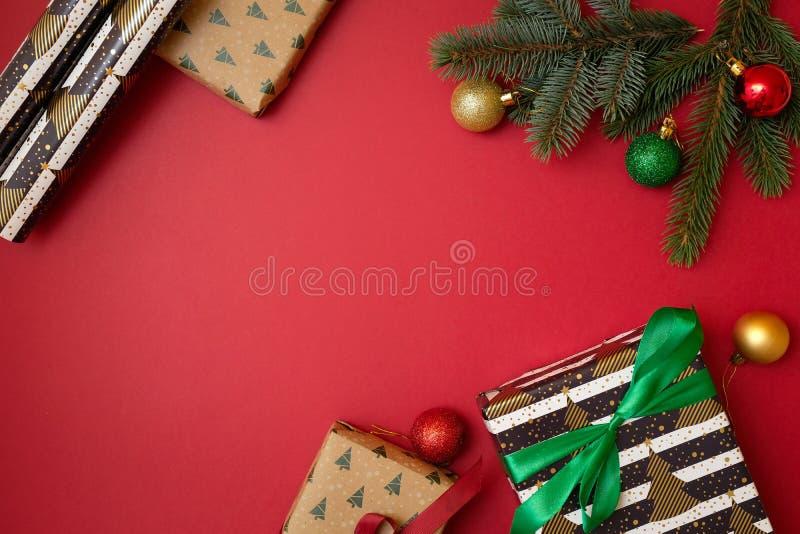 圣诞节在红色背景的假日构成与您的文本的拷贝空间 Xmas树与球在角落,美国兵的冷杉分支 免版税库存照片