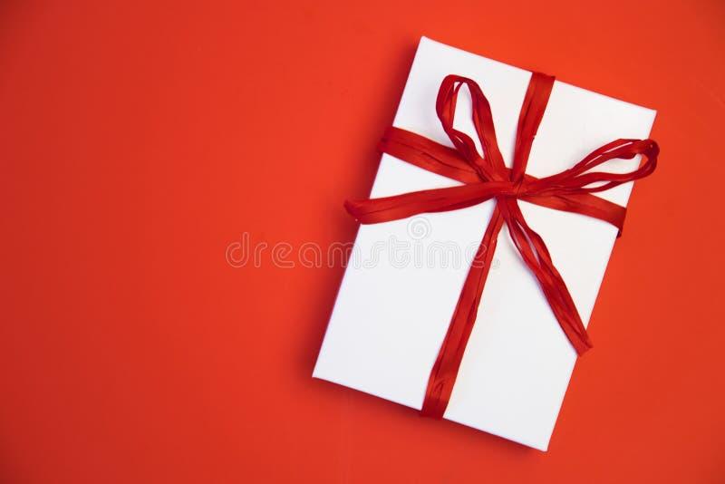 圣诞节在红色背景的礼物礼物 有丝带弓的简单,经典,红色和白色被包裹的礼物盒和 免版税库存图片
