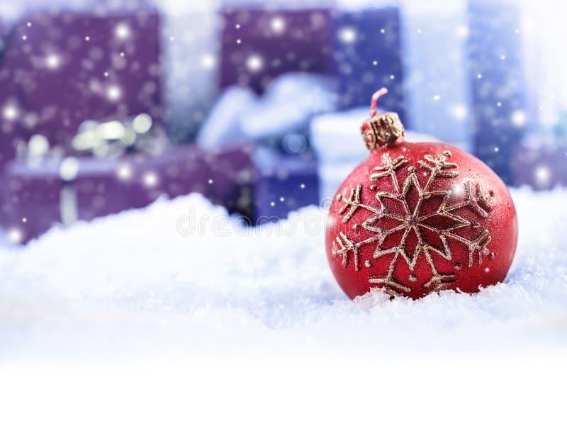 圣诞节在背景圣诞节礼物包裹的蜡烛球-下雪 免版税库存照片