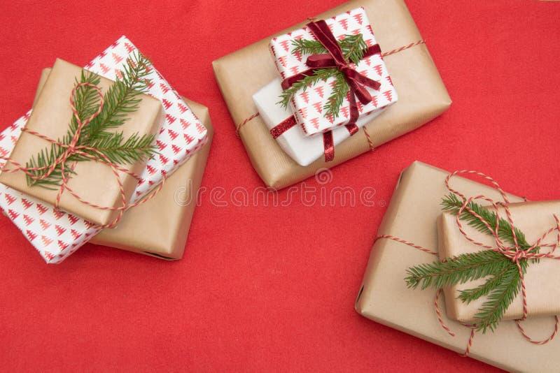 圣诞节在装饰品纸和装饰红色绳索丝带包裹的礼物盒红色表面上 创造性的爱好,顶视图 准备对X 免版税库存照片