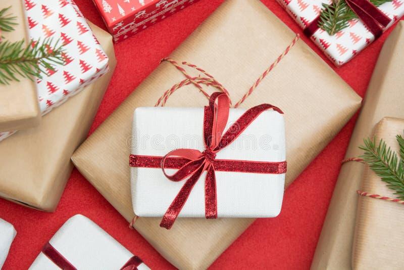 圣诞节在装饰品纸和装饰红色绳索丝带包裹的礼物盒红色表面上 创造性的爱好,顶视图 免版税库存照片