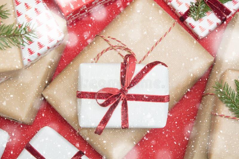 圣诞节在装饰品纸和装饰红色绳索丝带包裹的礼物盒红色表面上 创造性的爱好,顶视图 免版税库存图片
