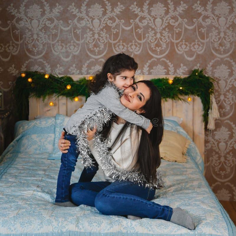 圣诞节坐床和拥抱小女儿的愉快的微笑的母亲家庭画象近对圣诞树在家 冬天 免版税库存照片