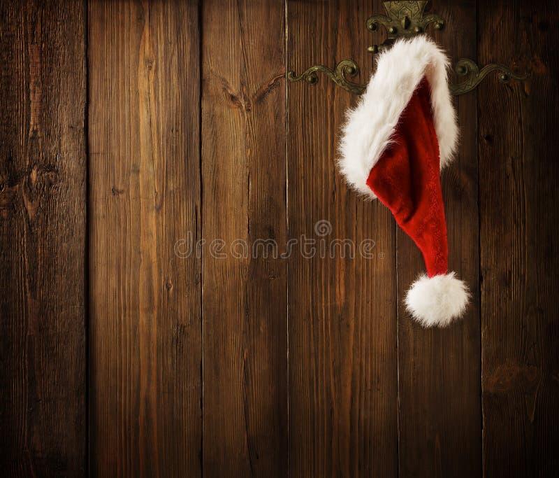 圣诞节垂悬在木墙壁, Xmas概念上的圣诞老人帽子 库存照片