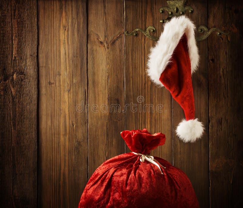 圣诞节垂悬在木墙壁, Xmas概念上的圣诞老人帽子 库存图片