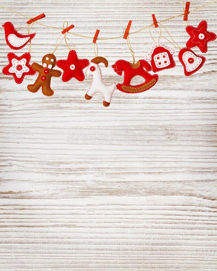 圣诞节垂悬白色木墙壁背景的装饰玩具 免版税库存照片