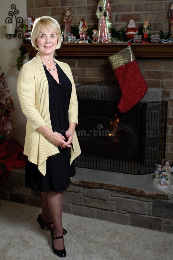 圣诞节壁炉微笑的妇女 免版税库存图片