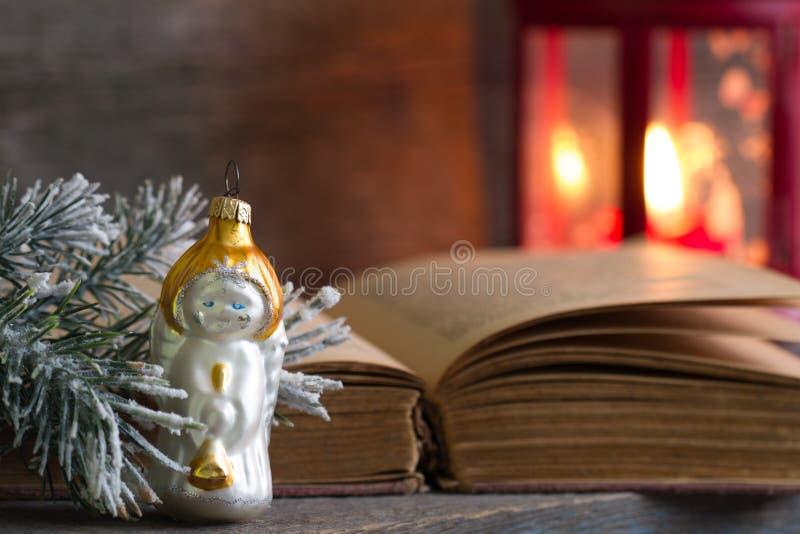 圣诞节天使圣经和灯笼在木背景 免版税库存图片