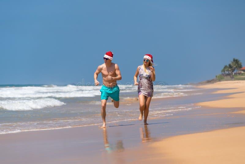 圣诞节夫妇愉快放松在跑在沙子的海滩 免版税库存照片