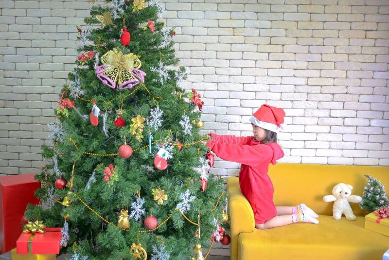 圣诞节女孩装饰圣诞树 孩子装饰Xmas树树愉快的孩子 E 儿童打开 免版税库存图片